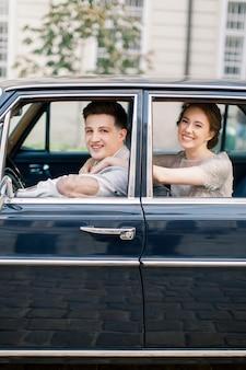 Sposa graziosa e sposo bello nella retro automobile nel vecchio centro urbano