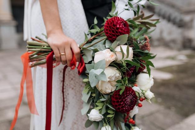 Sposa in abito bianco detiene un ricco bouquet di fiori rossi e bianchi