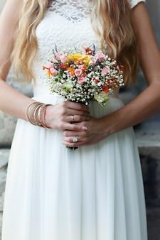 Sposa in abito bianco semplice pone con bouquet di fiori selvatici