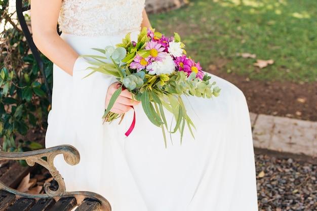 Sposa in abito da sposa bianco tenendo il bouquet di fiori in mano