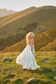 Sposa in abito da sposa vintage correndo via tramonto spettacolare paesaggio montano in background