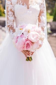 Sposa in abito ricco detiene il bouquet da sposa rosa di orchidee e peonie