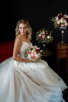 Sposa in piedi su un buio e in possesso di un mazzo di fiori rosa, fiori bianchi e verde con un nastro rosa