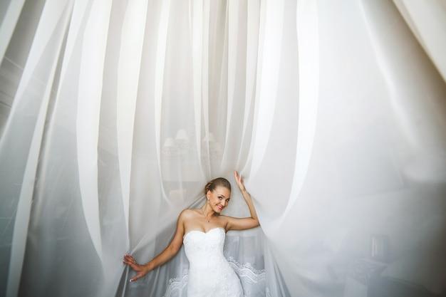 Sposa in posa con tende bianche
