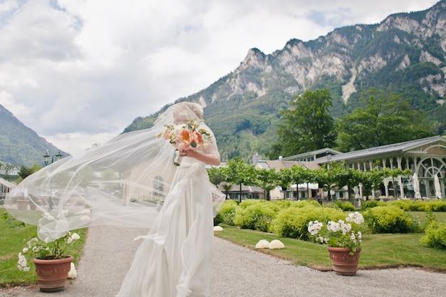 Sposa in un abito di pizzo con un velo che vola nel vento contro un bellissimo paesaggio alpino