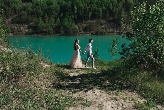 Sposa in un bel vestito tenendosi per mano con lo sposo in una tuta leggera contro il cielo blu e l'acqua blu. coppie di cerimonia nuziale che si levano in piedi su una collina sabbiosa all'aperto.