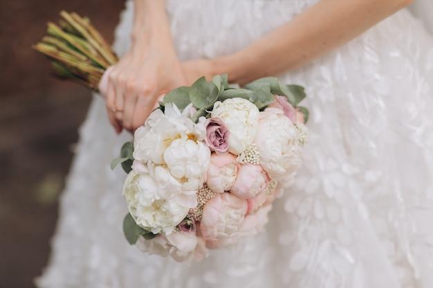 Sposa in vestito bianco che tiene il suo mazzo di nozze
