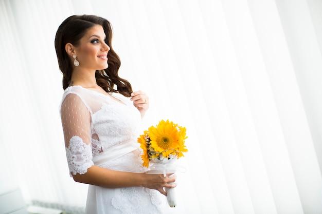 Sposa incinta con un mazzo di girasoli