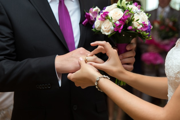 Sposa mettendo un anello sul dito dello sposo