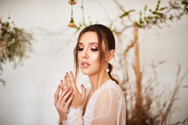 Sposa moderna che indossa in lingerie delicata la mattina del matrimonio. giovane donna molto piacevole su fondo bianco con i fiori naturali
