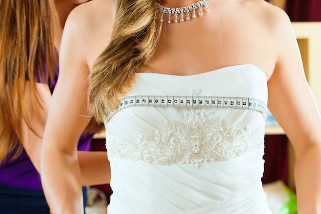 Sposa nel negozio di vestiti per abiti da sposa, sta scegliendo un vestito