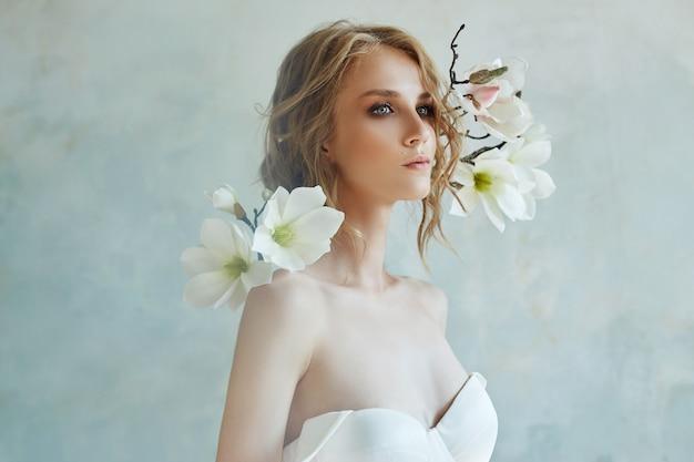 Sposa perfetta con gioielli, ritratto di una ragazza in un lungo abito bianco.