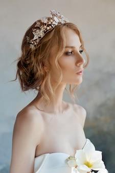 Sposa perfetta con gioielli, un ritratto di una ragazza in un lungo abito bianco.