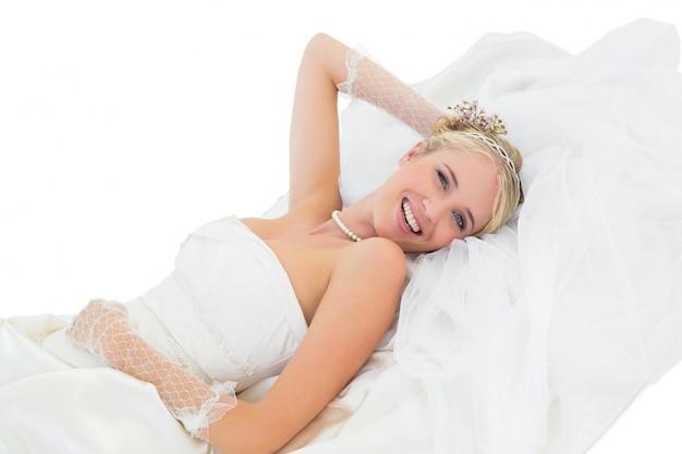 Sposa sensuale felice che si trova contro la priorità bassa bianca