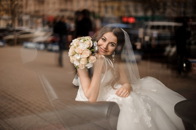 Sposa sorridente che si siede in una sedia nera di cuoio vicino alla finestra