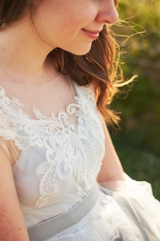 Sposa sorridente che tiene il bordo di un vestito