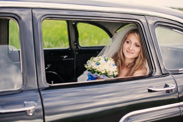 Sposa sorridente in macchina