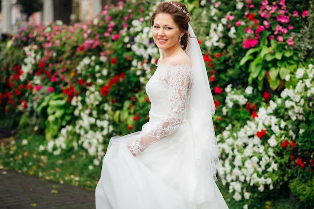 Sposa sorridente in un affascinante abito da sposa su uno sfondo di fiori colorati