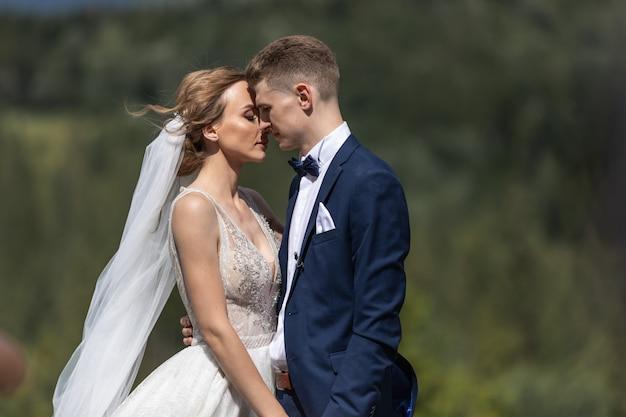 Sposa splendida e sposo alla moda che abbracciano e sorridono delicatamente. abbraccio sensuale degli sposi. momenti romantici di sposi.
