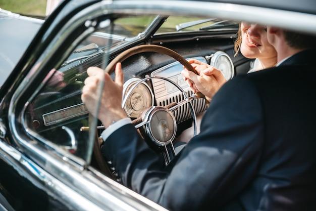 Spose felici stanno guidando in auto retrò