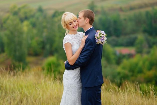 Sposi all'aperto in posizione natura. sposi in amore al giorno delle nozze.