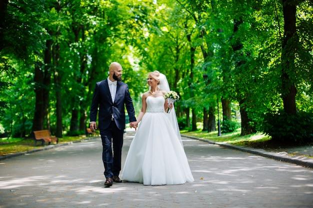 Sposi, bella giovane sposa e lo sposo in piedi in un parco all'aperto tenendosi per mano e sorridendo