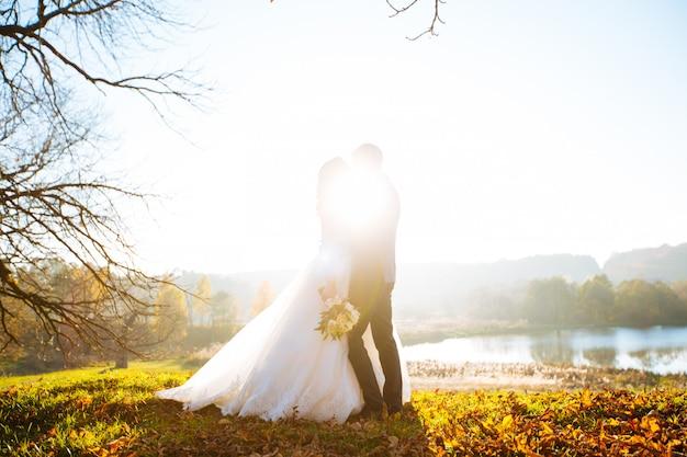 Sposi che baciano e che sorridono sul loro giorno delle nozze sulla passeggiata all'aperto. sposa divertente con bouquet di fiori.