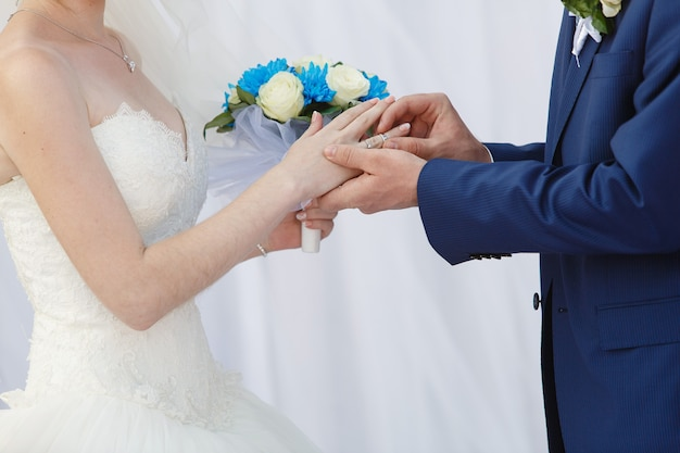 Sposi con anelli sulle dita al giorno delle nozze.