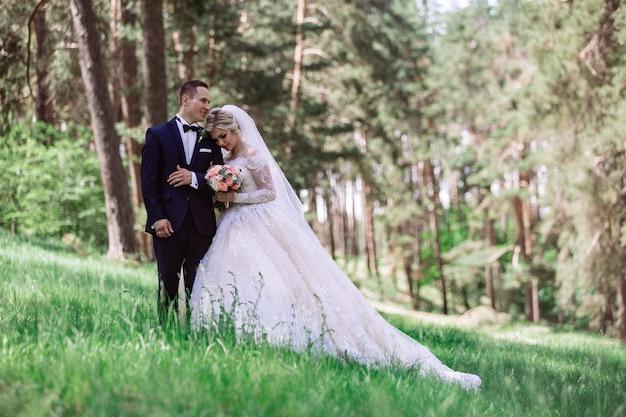 Sposi emotivi nel parco verde in spring.portrait della sposa e dello sposo in una giornata di sole all'aperto. sposa e lo sposo che abbraccia e sorride al giorno delle nozze in natura. bellissimi sposi camminano all'aperto