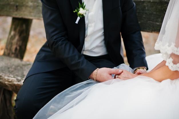 Sposi fantastici seduti su una panchina nel parco il giorno delle nozze.