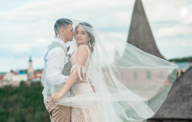 Sposi felici avvolti in un velo che si abbracciano sullo sfondo del castello