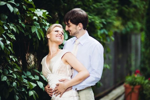Sposi felici che camminano nel parco il giorno delle nozze