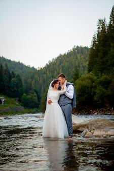 Sposi felici che stanno e che sorridono sul fiume. luna di miele, foto per san valentino