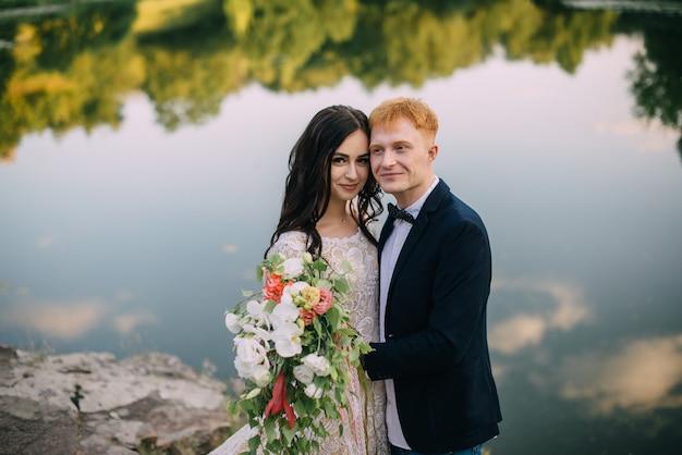 Sposi felici in piedi sulla riva del fiume
