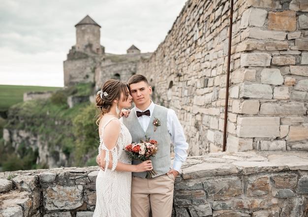 Sposi felici sul loro matrimonio vicino al vecchio castello