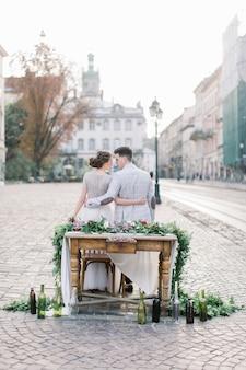 Sposi felici sulla cena romantica, seduto al tavolo di legno decorato. incredibile vecchia architettura di leopoli sullo sfondo