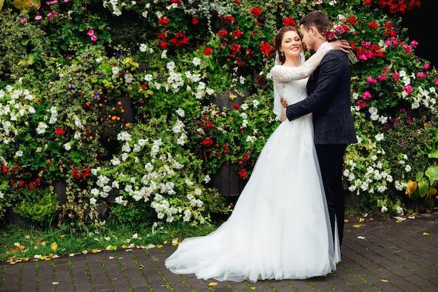 Sposi in piedi sullo sfondo del letto di fiori e gentil