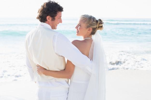 Sposi in piedi vicino al mare sorridendo a vicenda