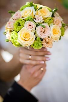 Sposi in possesso di un bellissimo bouquet da sposa nelle loro mani con indossando fedi nuziali