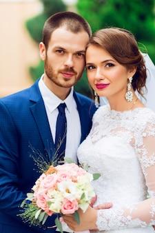 Sposi innamorati baci e sorridenti. giovane sposa abbastanza elegante e il suo bel sposo in posa nel verde del parco.