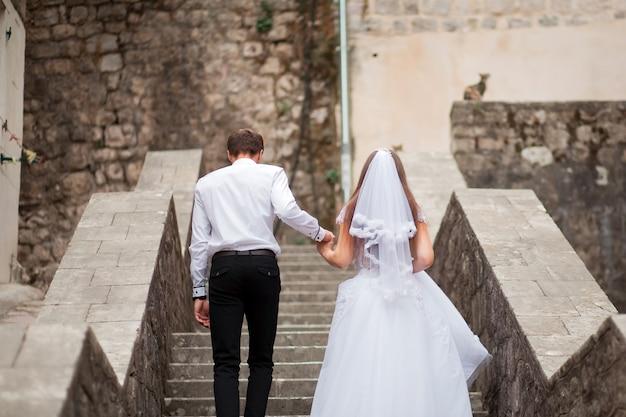 Sposi la sposa in abito e sposo a piedi lungo la strada della vecchia città tenendosi per mano