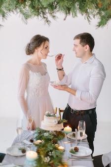 Sposi mangiare la torta nuziale decorata con pino, bacche e fiori di cotone con le loro damigelle e groomsmen