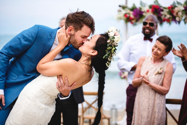 Sposi novelli allegri al cerimoniale di nozze della spiaggia