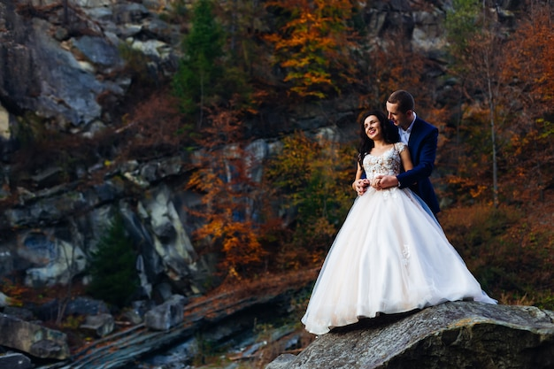 Sposi novelli su una grande pietra senza sfondo di rocce e alberi