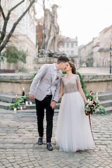 Sposi romantici in amore, camminando e baciando, tenendosi per mano. decorazioni di nozze sulle scale di pietra, monumento, antichi edifici sullo sfondo