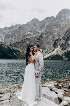 Sposi romantici in amore in piedi sulla riva pietrosa del lago sea eye in polonia. vista panoramica sulle montagne. la sposa e lo sposo. morskie oko. monti tatra.