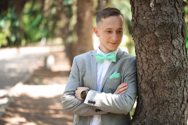 Sposo allo smoking di nozze che sorride e che aspetta sposa. sposo ricco al giorno del matrimonio. sposo elegante in costume e cravatta a farfalla.