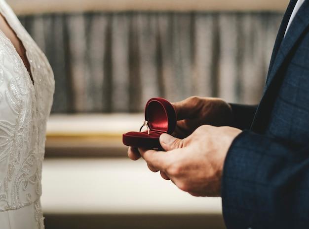 Sposo alzando una scatola con l'anello di nozze
