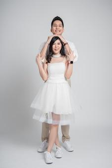 Sposo asiatico delle giovani coppie felici che abbraccia la sua sposa in vestito da sposa casuale