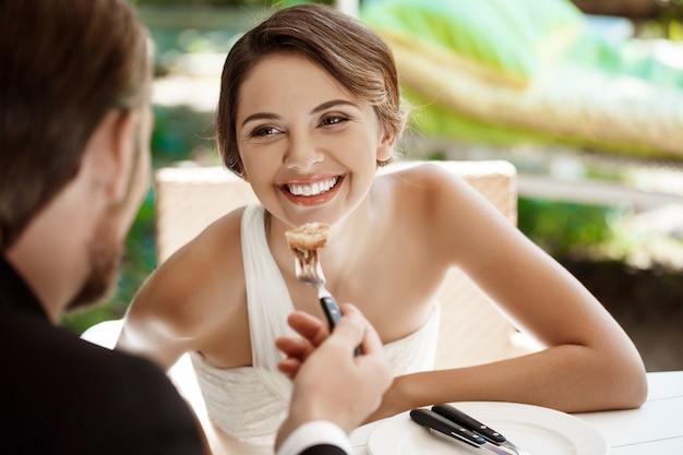 Sposo bello che alimenta la sua sposa di croissant in caffè.